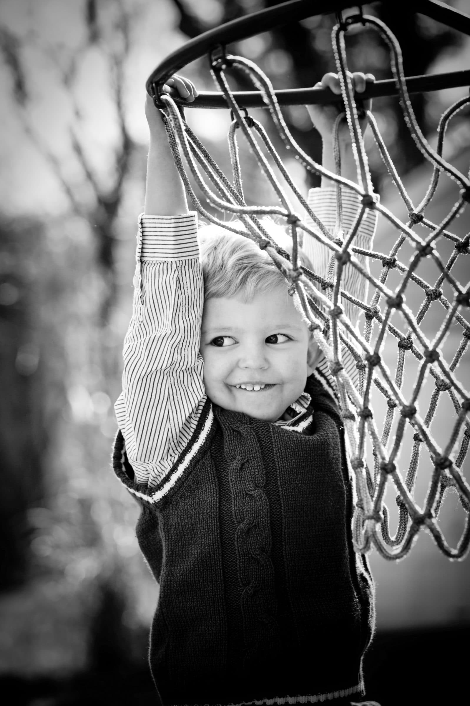boy hanging from basketball net