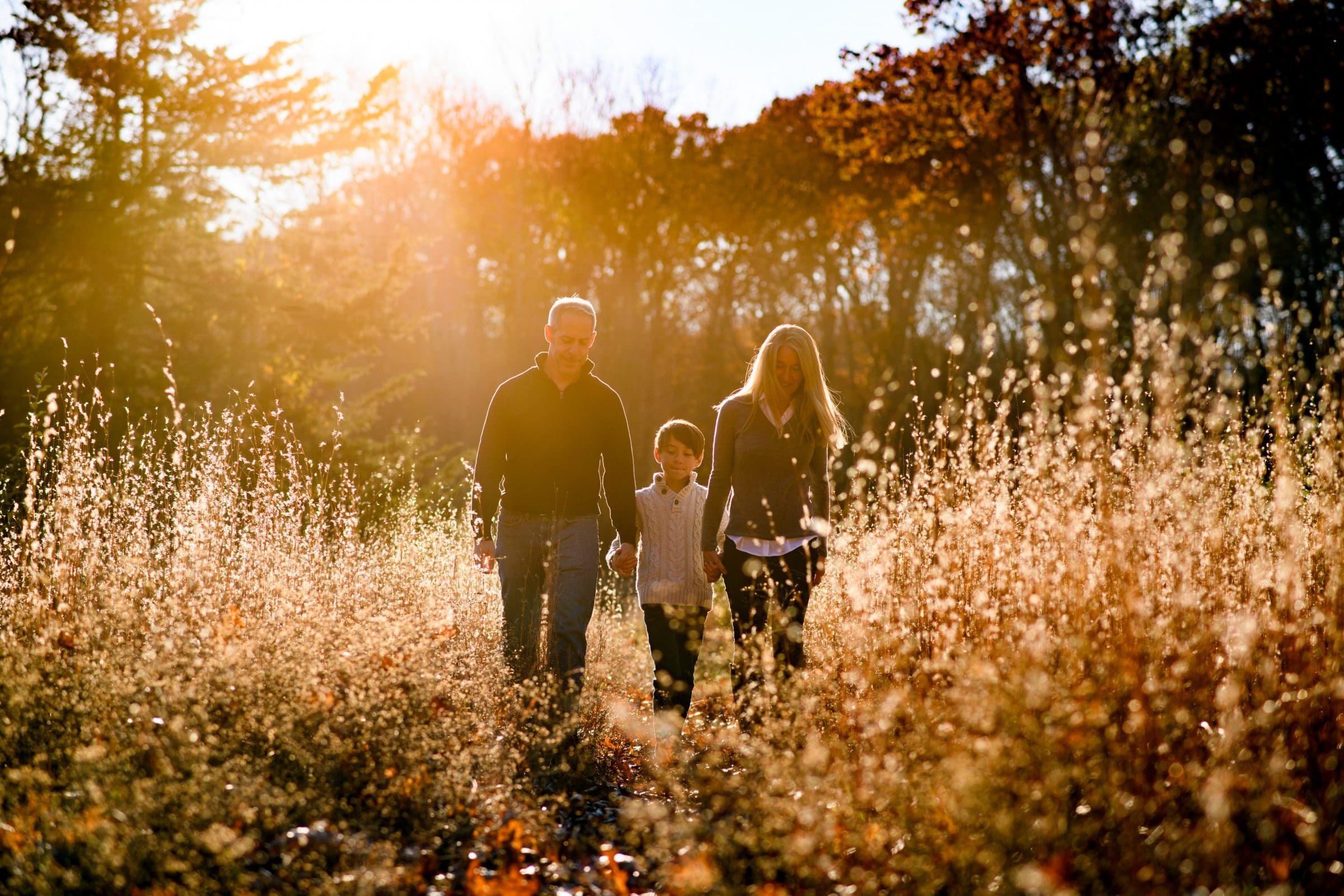 family of 3 walking through tall grasses during golden hour