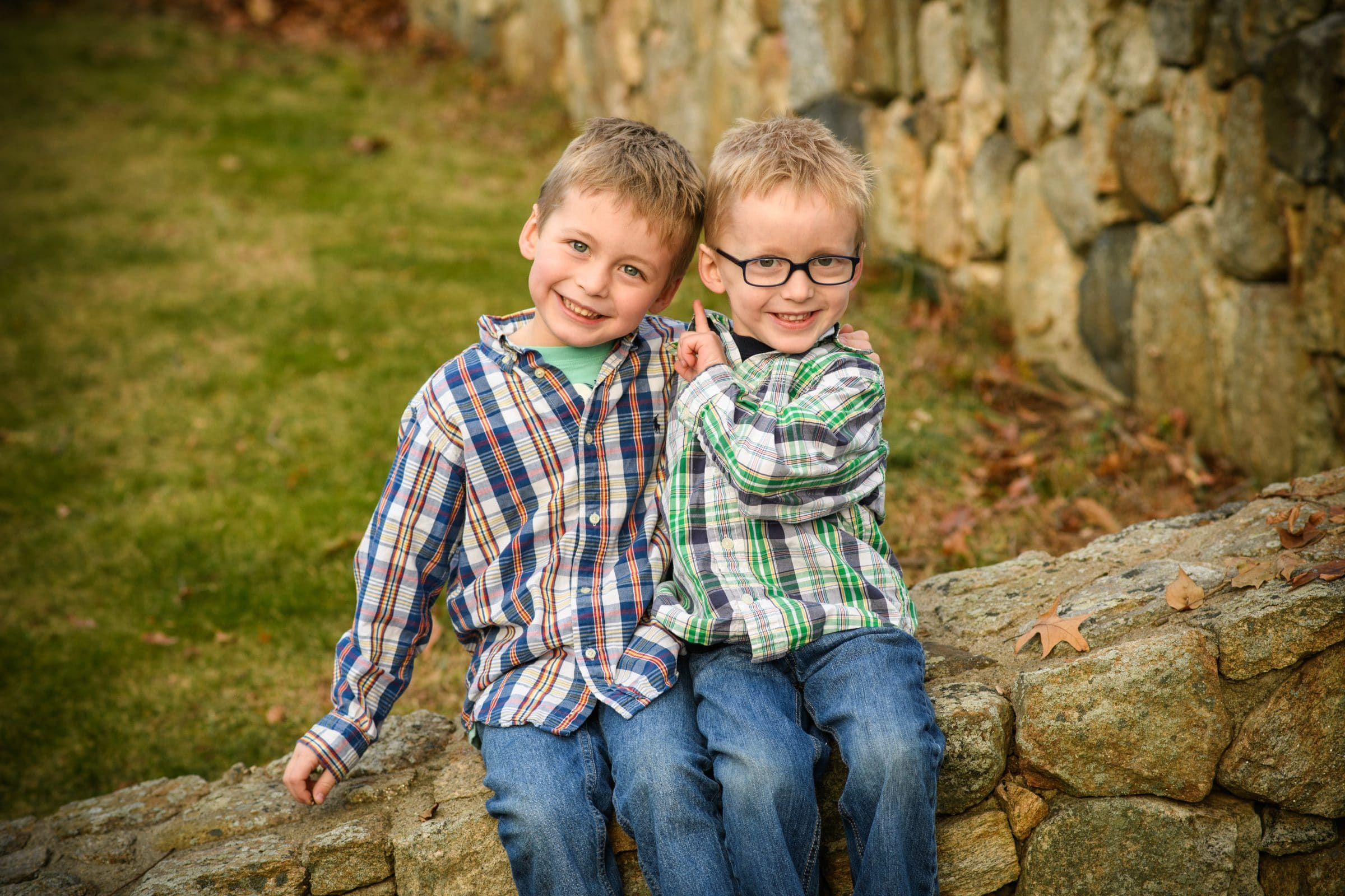 2 brothers sitting on stone wall