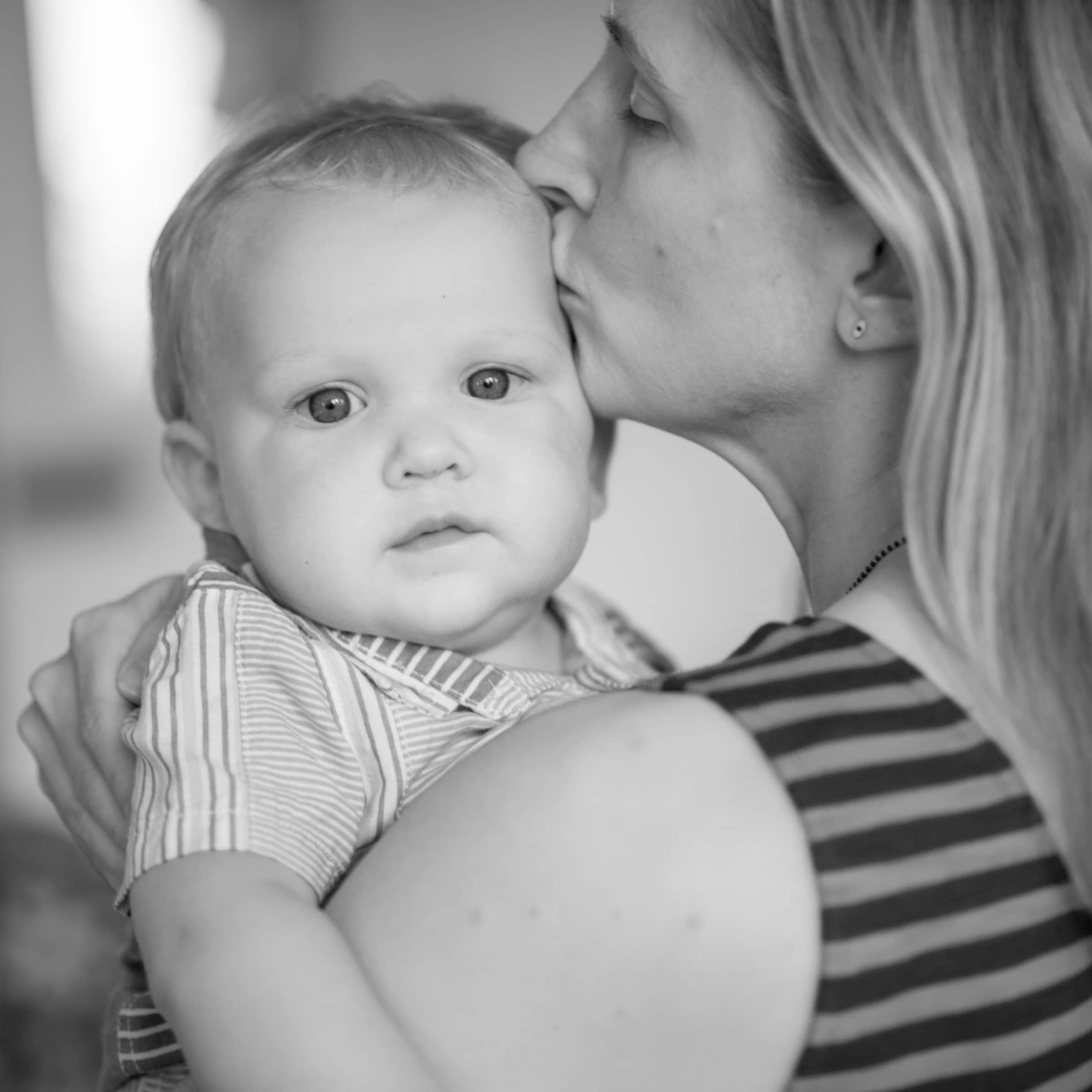 mom kissing infant on the forehead